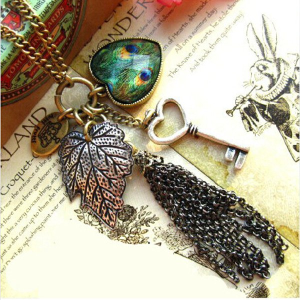 Bronzeweinlese Pfau Feder Herz Blatt Schlüssel Troddel Strickjacke Halskette Damenschmuck